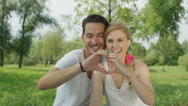 CLOSE UP: Young devoted couple sitting in park and making heart with fingers Stock Footage