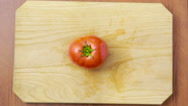 Woman cuts a tomato on a wooden board. view from above Stock Footage