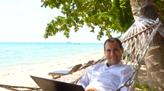 Young man work on laptop relaxing in hammock with seaview Stock Footage