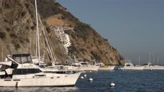 Zoom out of a dry barren Mediterranean climate with yachts on mooring balls Stock Footage