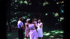 1963: small group of people and a baby have gathered in the grass Stock Footage