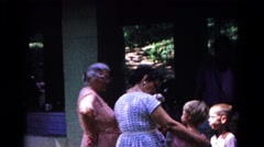 1963: two women smile and laugh at two children outside a house. COLD SPRINGS Arkistovideo