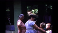 1963: two women smile and laugh at two children outside a house. COLD SPRINGS Stock Footage