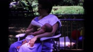 1963: woman in blue dress sits while feeding a baby with a bottle COLD SPRINGS Stock Footage
