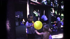 1963: three little boys playing with balloons in a public area on a sunny day. Stock Footage