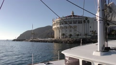 Front of the catamaran in foreground and Casino Avalon with rock jetty Stock Footage