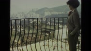 1974: woman enjoys her balcony view of city INDIA Stock Footage