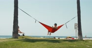 Man Swinging on Hammock Between Palm Trees at Venice Beach Stock Footage