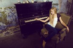 Pretty young blond real girl at piano in old-style rusted interior, vintage Stock Photos