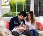 Young couple feeding their infant son on white sofa Stock Photos