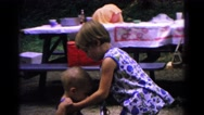 1963: little girl helping her baby brother in his seat at a park outing  Stock Footage
