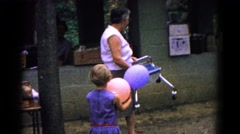 1963: a women outside at a picnic carrying a child's seat COLD SPRINGS, NEW YORK Stock Footage
