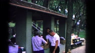 1963: family having a serious talk during bbq at a park  Stock Footage