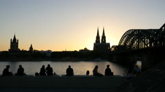 People enjoying the sunset on Promenade in Cologne with view of the Cathedral Stock Footage