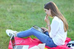 Young girl sitting grass in the park works at a laptop and eating fast food Stock Photos