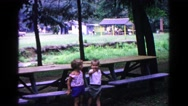 1963: two small children as they stand next to a picnic table on a park Stock Footage