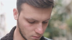 Attractive young man with serious gaze looking into the camera: 4k footage Stock Footage