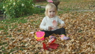 Cute baby girl playing with leaves in autumn Stock Footage
