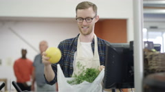 4K Portrait smiling grocery store worker packing customer's bag at the checkout Stock Footage