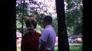 1963: lovers sneaking off get caught embarrassed at summer forested park  Stock Footage
