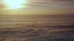 Fierce wind blows snow across tundra at golden sunset Stock Footage