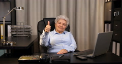 Old Woman Posing Serious Looking Camera Showing Thumb Up Sign Inside Office Room Stock Footage