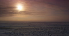 Sun shines through clouds on snow blowing across empty tundra Stock Footage