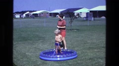 1975: a little boy playing in the pool with a hose while his mother stands by Stock Footage
