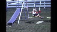1975: a small child with a red balloon swing on a swing set CALIFORNIA Stock Footage