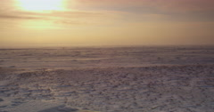 Wide sun setting over blizzard scoured tundra in orange Stock Footage