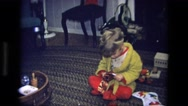 1975: child opening a present and showing it while sitting on the carpet  Stock Footage