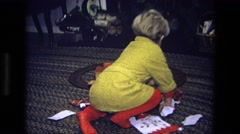 1975: a little boy in pajamas opening a gift on the wrapping paper covered floor Stock Footage