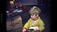 1975: a little boy opening his presents on christmas day with his family Stock Footage