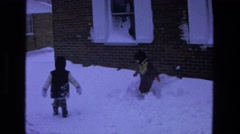 1975: two children bundled in winter clothes trudge through snow  Stock Footage