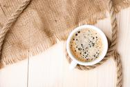 Cup of coffee with foam on wooden table Stock Photos