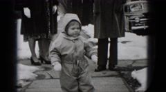 1948: a child dressed in a skiing suit is walking on the sidewalk amongst other Stock Footage