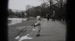 1948: cute boy winter jumpsuit walking in barren park landscape MIDDLETOWN Stock Footage