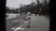 1948: cute boy winter jumpsuit walking in barren park landscape MIDDLETOWN Stock Footage