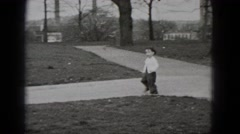 1948: a little boy running and trying to catch a white dove in the park Stock Footage