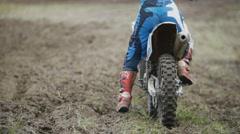 Motocross racer start riding his dirt Cross MX bike kicking up dust rear view Stock Footage