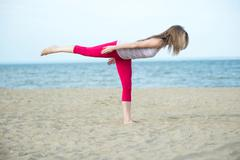 Young lady practicing yoga. Workout near ocean sea coast Stock Photos