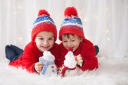 Sweet children, brother boys, playing with handmade snowmen at home Stock Photos