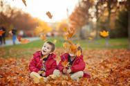 Two kids, boy brothers, playing with leaves in autumn park Stock Photos