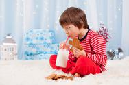 Cute little happy boy, eating cookies and drinking milk, waiting for Santa Stock Photos