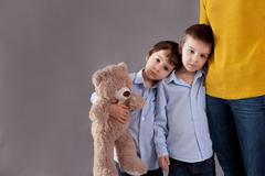 Sad little children, boys, hugging their mother at home, isolated image, copy Stock Photos