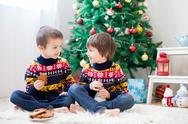 Two adorable children, boy brothers, eating cookies and drinking milk at home Stock Photos