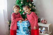Two sweet children, boy brothers, opening presents Stock Photos