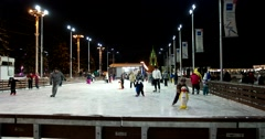 Kids learn to skate, ice-skating rink at ENEA, evening illumination Stock Footage