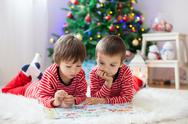 Two boys, reading a book in front of Christmas tree Stock Photos
