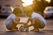 Two sweet children, boy brothers, playing with car toys on the street in vill Stock Photos
